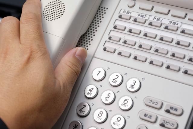 写真:受話器をとる手