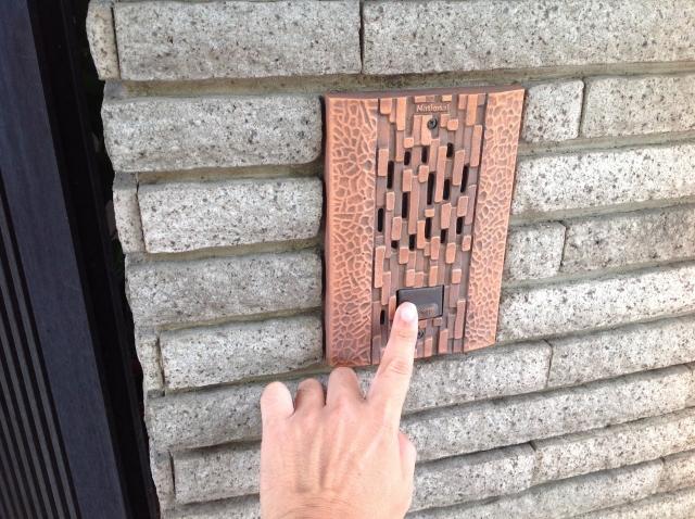 写真:家のインターホンを押す営業マン