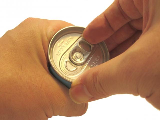 写真:缶コーヒーを空ける手